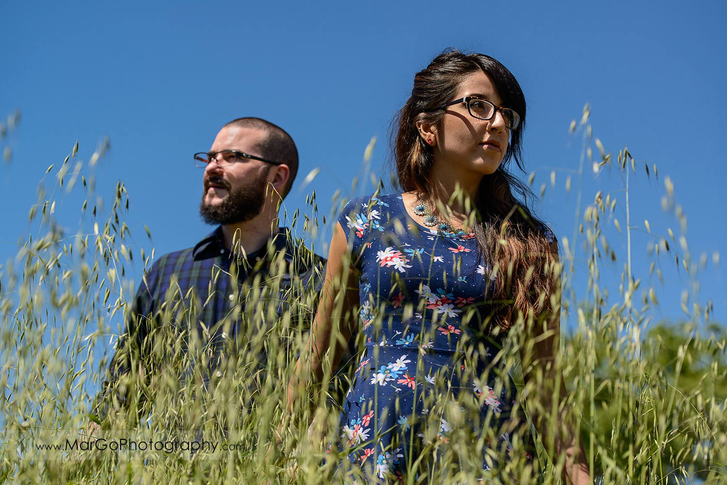 woman in blue dress and man in blue shirt walking in the grass during engagement session at Sunol Regional Wilderness