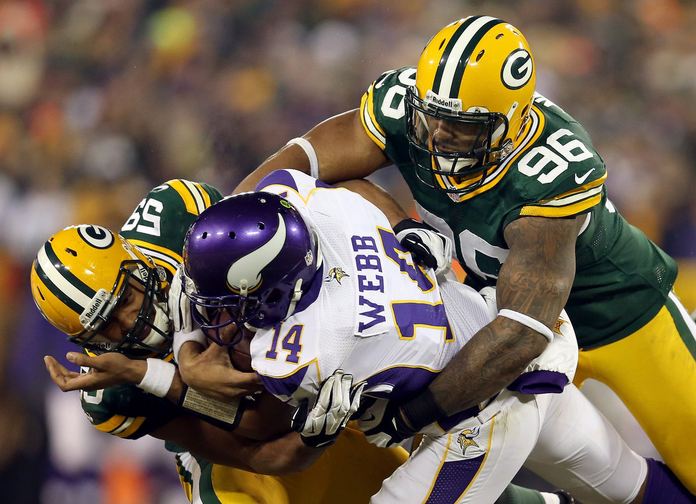 Description of . Quarterback Joe Webb #14 of the Minnesota Vikings is tackled by inside linebacker Brad Jones #59 and defensive tackle Mike Neal #96 of the Green Bay Packers in the fourth quarter during the NFC Wild Card Playoff game at Lambeau Field on January 5, 2013 in Green Bay, Wisconsin.  (Photo by Andy Lyons/Getty Images)