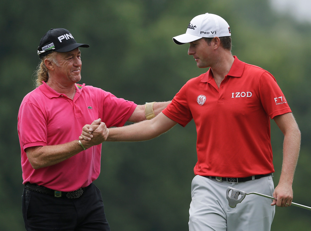 . Miguel Angel Jimenez, of Spain, left, greets Webb Simpson on the ninth green during the second round of the PGA Championship golf tournament at Oak Hill Country Club, Friday, Aug. 9, 2013, in Pittsford, N.Y. (AP Photo/Patrick Semansky)