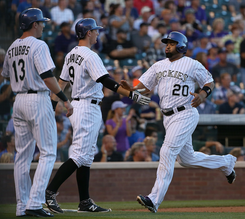 . DENVER, CO - AUGUST 05:  Wilin Rosario #20 of the Colorado Rockies scores on a double by Brandon Barnes #1 of the Colorado Rockies and celebrates with Drew Stubbs #13 and DJ LeMahieu #9 of the Colorado Rockies to take a 2-0 lead over the Chicago Cubs in the second inning at Coors Field on August 5, 2014 in Denver, Colorado.  (Photo by Doug Pensinger/Getty Images)