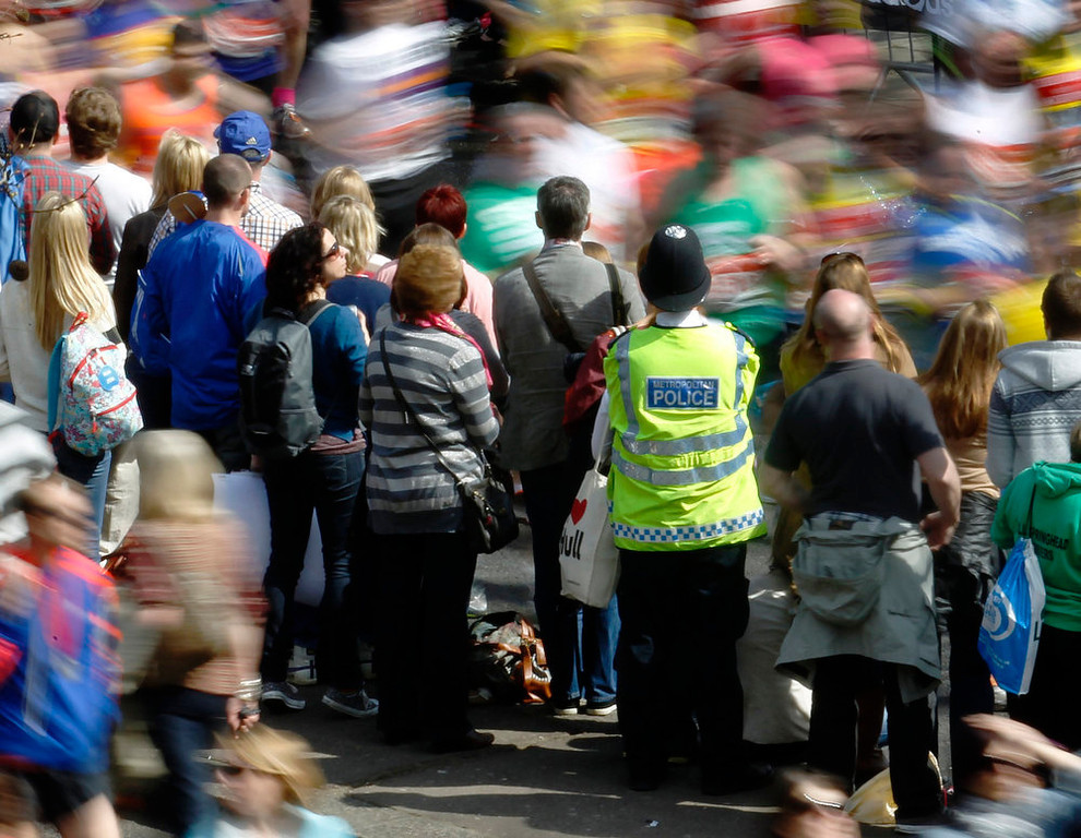 . A police officer observes runners and crowd during the London Marathon April 21, 2013. Undaunted by the Boston Marathon bombings, big crowds lined the route of London \'s mass road race on Sunday to cheer on around 36,000 runners, many of whom wore black ribbons to remember the dead and wounded. REUTERS/Luke MacGregor