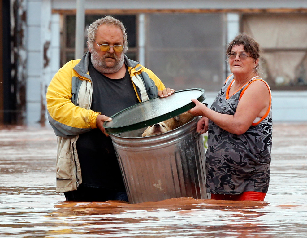 . George and Susan Kruger make one of three trips with their animals from their flooded house to safety on Sunday, May 24, 2015 in Purcell, Okla. Rising water from overnight rains began to rise early in the morning.  The Krugers refused to leave their home and made several trips to retrieve five dogs and a baby chick. (Steve Sisney/The Oklahoman via AP) LOCAL STATIONS OUT (KFOR, KOCO, KWTV, KOKH, KAUT OUT); LOCAL WEBSITES OUT; LOCAL PRINT OUT (EDMOND SUN OUT, OKLAHOMA GAZETTE OUT) TABLOIDS OUT