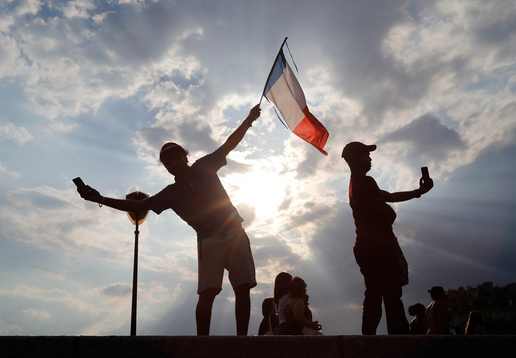 . People take a selfie after France won the World Cup final between France and Croatia, Sunday, July 15, 2018 in Paris. France won its second World Cup title by beating Croatia 4-2. (AP Photo/Laurent Cipriani)
