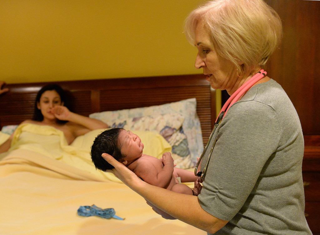 . Midwife Simona Istrate hands Nicholas over to Lilibeth and Luis Salas, of El Monte, at the Natural Birth Center and Women\'s Wellness in Whittier on December 29, 2013. Birthing centers and home births are becoming more popular and the Birth Center in Whittier is doing so well it opened a second office in Beverly Hills. (Staff Photo by Keith Durflinger/Whittier Daily News)