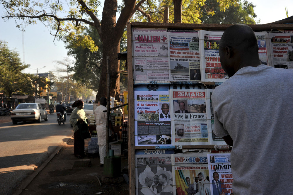 Description of . A resident looks at newspapers\' frontpages focusing on France\'s military intervention to turn back the terrorist threat in Mali on January 14, 2013 in Bamako. ISSOUF SANOGO/AFP/Getty Images