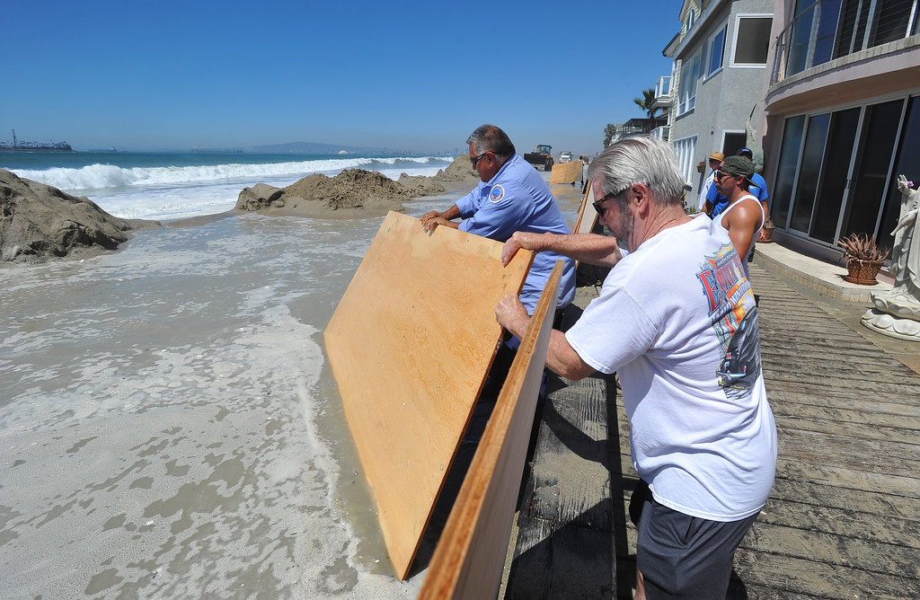 . Plywood sheets are placed against a wall to try to stop water from splashing over as high tide and a storm surge from Hurricane Marie had locals bracing for the worst in the Peninsula neighborhood in Long Beach, CA on Wednesday, August 27, 2014. With city crews constantly building a sand berm, the water was held back from the homes and streets during the morning high tide. (Photo by Scott Varley, Daily Breeze)