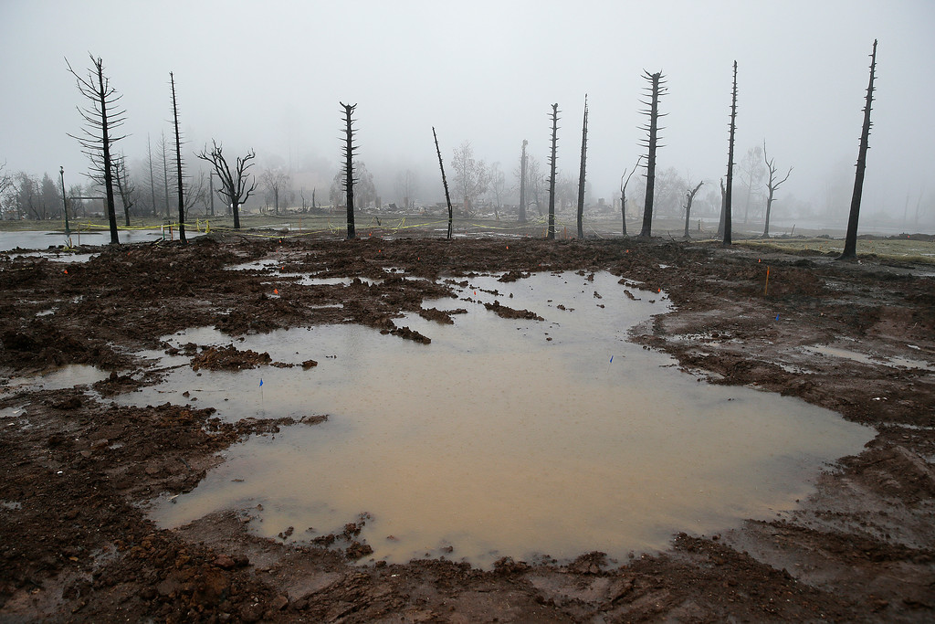 . Rain water pools where a Fountaingrove neighborhood home once stood Monday, Jan. 8, 2018, in Santa Rosa, Calif. Storms brought rain to California on Monday and increased the risk of mudslides in fire-ravaged communities in devastated northern wine country and authorities to order evacuations farther south for towns below hillsides burned by the state\'s largest-ever wildfire. (AP Photo/Eric Risberg)