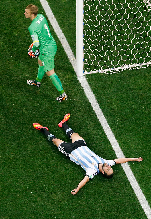 . Argentina\'s Gonzalo Higuain lies on the pitch after missing a chance as Netherlands\' goalkeeper Jasper Cillessen (1) holds the ball during the World Cup semifinal soccer match between the Netherlands and Argentina at the Itaquerao Stadium in Sao Paulo, Brazil, Wednesday, July 9, 2014. (AP Photo/Fabrizio Bensch, Pool)