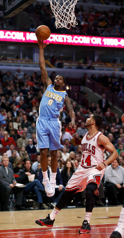 . Denver Nuggets guard Aaron Brooks (0) scores past Chicago Bulls guard D.J. Augustin during the first half of an NBA basketball game Friday, Feb. 21, 2014, in Chicago. (AP Photo/Charles Rex Arbogast)