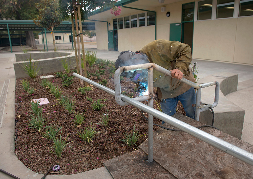 . A worker welds new handrails at Rowland Elementary School\'s newly remodeled campus August 7, 2013.   (SGVN/Staff photo by Leo Jarzomb)