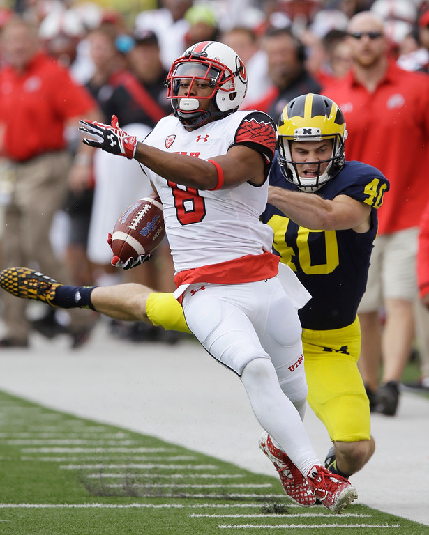 . Utah\'s Kaelin Clay (8), defended by Michigan punter Will Hagerup (40) returns the Michigan punt for a 66-yard touchdown during the first half of an NCAA college football game in Ann Arbor, Mich., Saturday, Sept. 20, 2014. (AP Photo/Carlos Osorio)