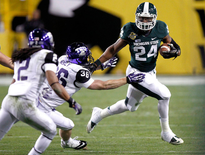 . Michigan State running back Le\'Veon Bell, right, stiff-arms TCU linebacker Joel Hasley, center, as TCU cornerback Jason Verrett, left, pursues during the first half of the Buffalo Wild Wings Bowl NCAA college football game Saturday, Dec. 29, 2012, in Tempe, Ariz. (AP Photo/Paul Connors)