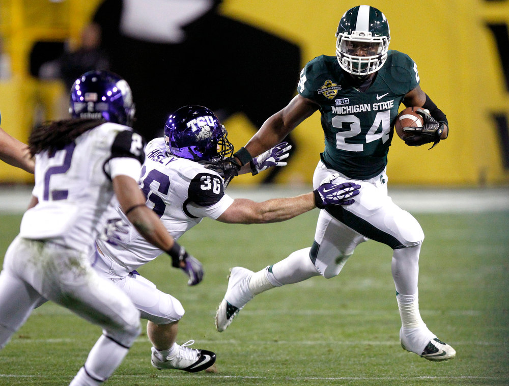Description of . Michigan State running back Le'Veon Bell, right, stiff-arms TCU linebacker Joel Hasley, center, as TCU cornerback Jason Verrett, left, pursues during the first half of the Buffalo Wild Wings Bowl NCAA college football game Saturday, Dec. 29, 2012, in Tempe, Ariz. (AP Photo/Paul Connors)