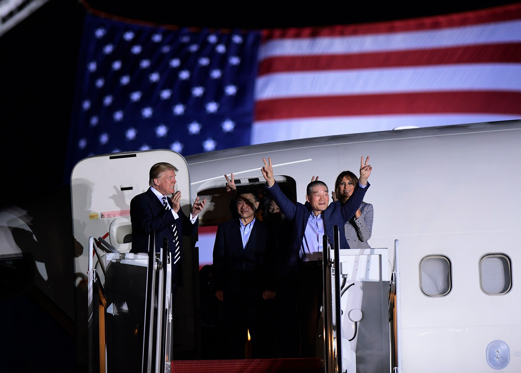 . President Donald Trump, from left, greets Tony Kim, Kim Hak Song, seen in the shadow, and Kim Dong Chul, three Americans detained in North Korea for more than a year, as they arrive at Andrews Air Force Base in Md., Thursday, May 10, 2018. First lady Melania Trump also greets them at right. (AP Photo/Susan Walsh)