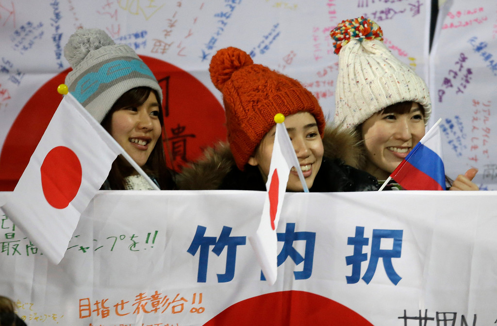 . Japan supporters smile as they wait for the beginning of the men\'s normal hill ski jumping final at the 2014 Winter Olympics, Sunday, Feb. 9, 2014, in Krasnaya Polyana, Russia. (AP Photo/Gregorio Borgia)
