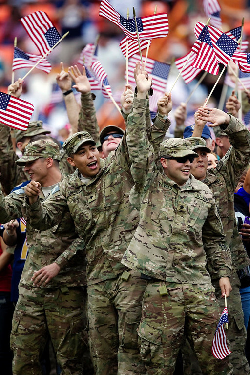 . Members of the military wave United States flags on the field during the halftime show of the NFL football Pro Bowl game in Honolulu, Sunday, Jan. 27, 2013. (AP Photo/Marco Garcia)
