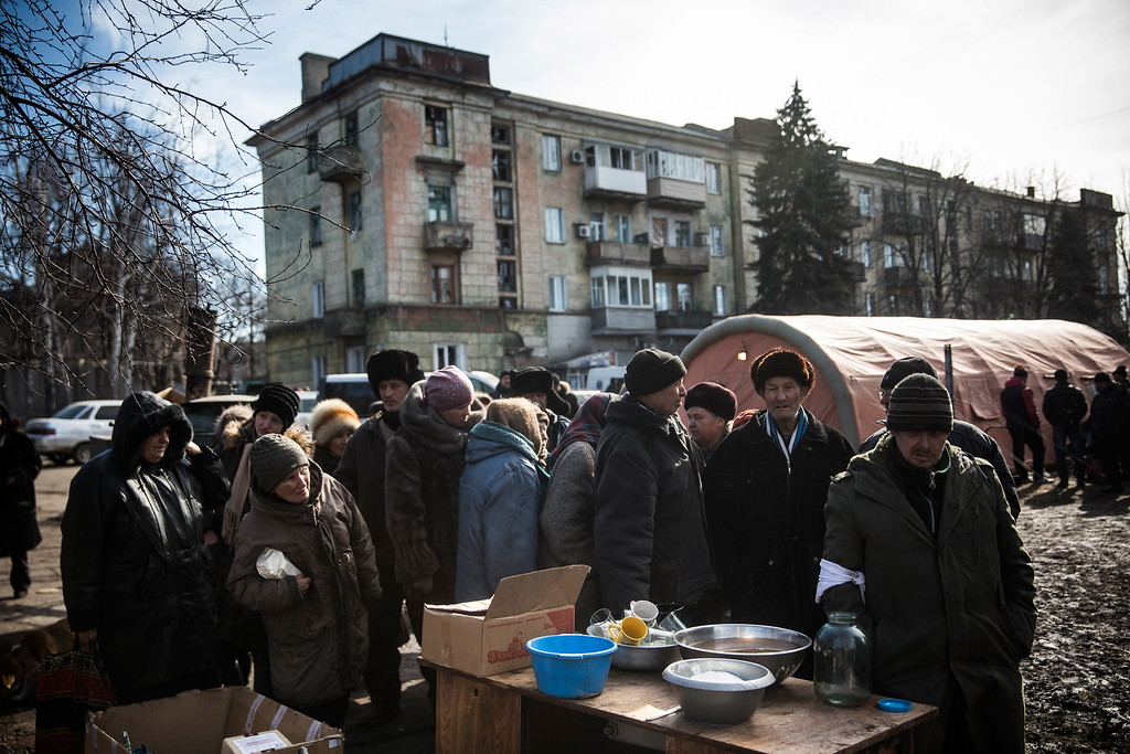 . DEBALTSEVE, UKRAINE - FEBRUARY 25:  Civilians wait for hot tea to be served by Russian backed rebels on February 25, 2015 in Debaltseve, Ukraine. After approximately one month of fighting, Russian backed rebels successfully forced Ukrainian troops to withdraw from the town of 100,00 people on February 18. Only approximately 11,000 civilians remain in the town. Debaltseve is considered an asset to both Ukrainians and the rebels due to the railway station and it\'s connection to other eastern Ukranian towns.  (Photo by Andrew Burton/Getty Images)