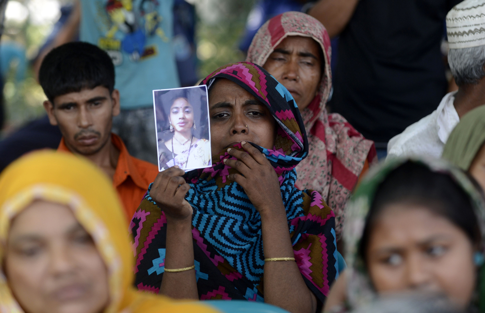 . A Bangladeshi mourner and relative of a victim of the Rana Plaza building collapse holds up a photograph as she takes part in a protest marking the first anniversary of the disaster at the site where the building once stood in Savar on the outskirts of Dhaka on April 24, 2014. The Rana Plaza building collapsed on April 24, 2013, killing 1138 workers in the world\'s worst garment factory disaster. Western fashion brands faced pressure to increase help for victims as mass protests marked the anniversary. Thousands of people, some wearing funeral shrouds, staged demonstrations at the site of the now-infamous Rana Plaza factory complex. (MUNIR UZ ZAMAN/AFP/Getty Images)