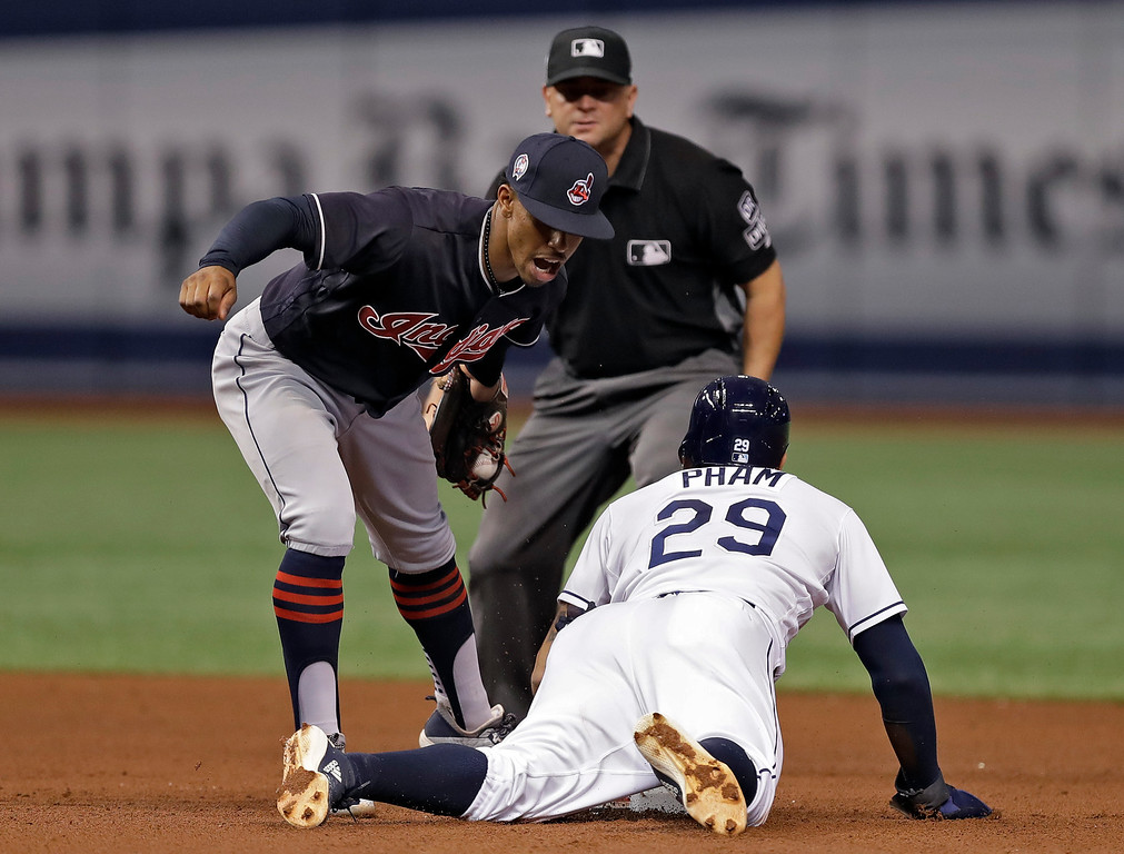 . Tampa Bay Rays\' Tommy Pham (29) steals second base ahead of the tag by Cleveland Indians shortstop Francisco Lindor during the fourth inning of a baseball game, Tuesday, Sept. 11, 2018, in St. Petersburg, Fla. Umpire Scott Barry looks on. (AP Photo/Chris O\'Meara)