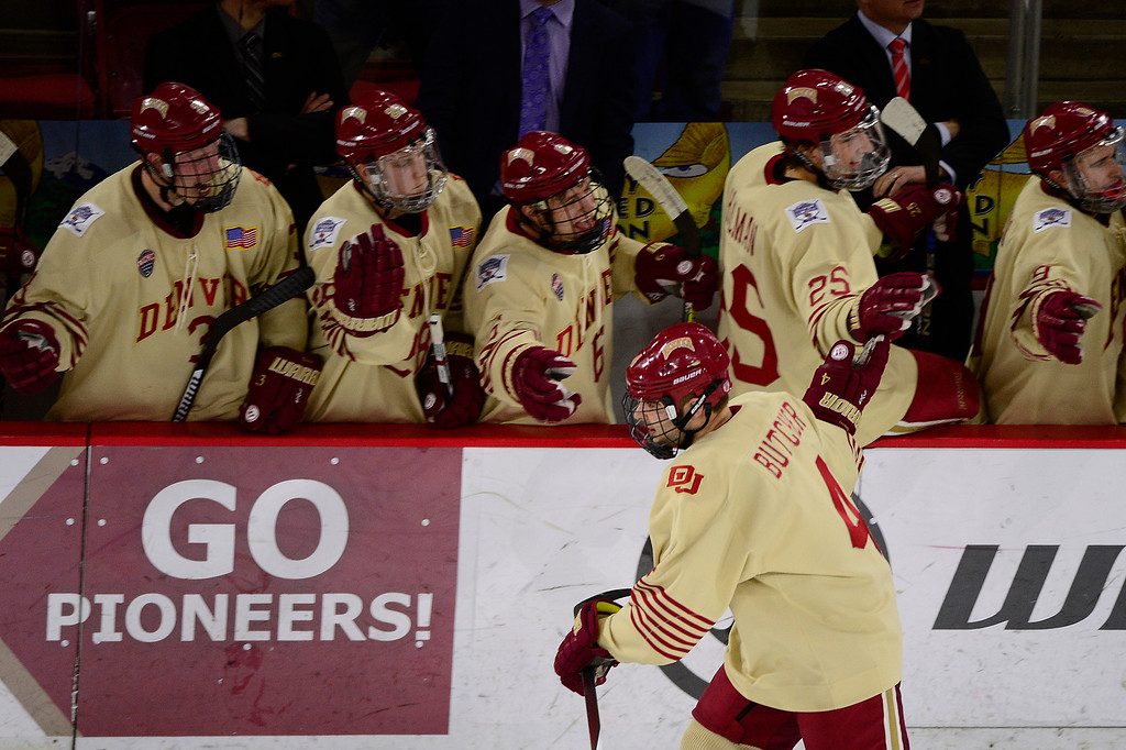 . Denver Pioneers defenseman Will Butcher (4) high fives teammates after scoring during the second period at Magness Arena on March 4, 2016 in Denver, Colorado. (Photo by Brent Lewis/The Denver Post)