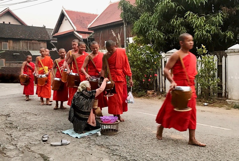 It is a quiet, meditative ceremony through which monks demonstrate their vows of poverty and humility while lay Buddhists gain spiritual merit by the act of respectful giving. - Buddhist Monk Alms Giving ceremony - Luang Prabang, Laos