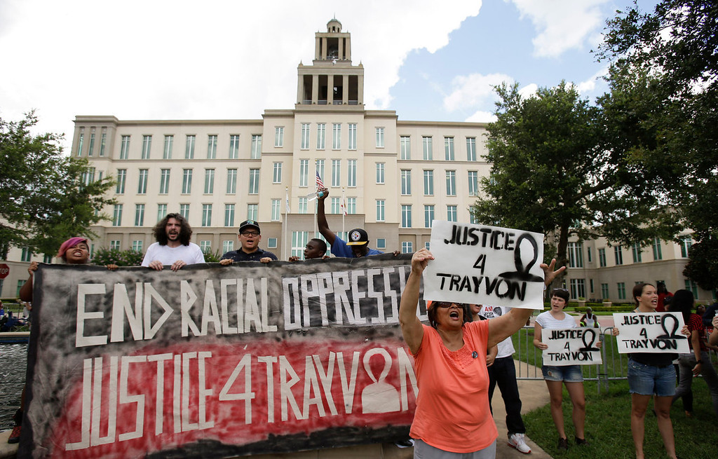 . Demonstrators shout slogans in front of the Seminole County Courthouse during jury deliberations in the trial of George Zimmerman, Saturday, July 13, 2013, in Sanford, Fla. Zimmerman has been charged with the 2012 shooting death of Trayvon Martin. (AP Photo/John Raoux)
