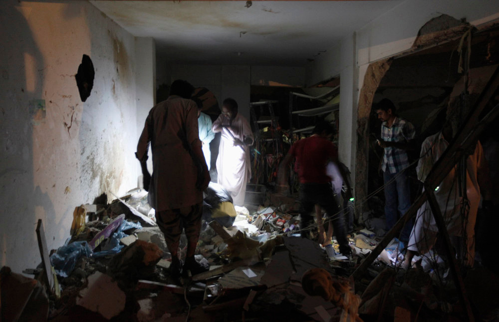 . Residents search for their belongings after a bomb blast in a residential area in Karachi March 3, 2013. A bomb attack in a Shi\'ite Muslim area of Pakistan\'s commercial capital Karachi killed 25 people and wounded 50 on Sunday, the police said. REUTERS/Akhtar Soomro