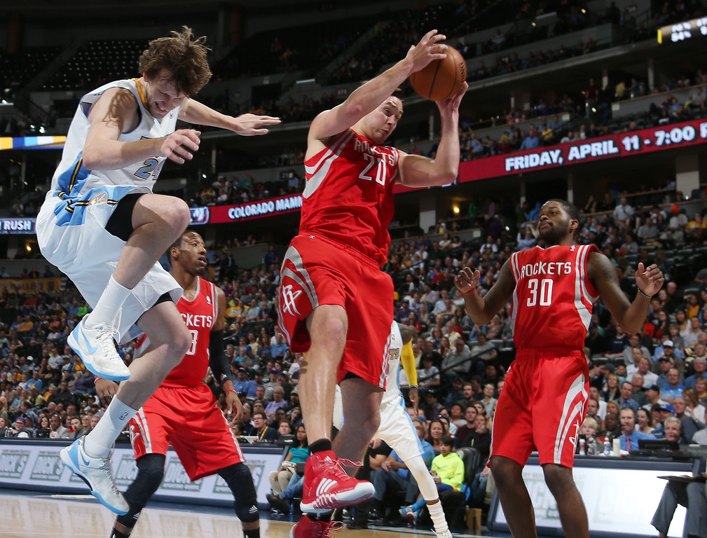 . Houston Rockets forward Donatas Motiejunas, center, of Lithuania, pulls down a rebound between Denver Nuggets forward jan Vesely, of the Czech Republic, left, and Rockets guard Troy Daniels in the fourth quarter of the Nuggets\' 123-116 victory in an NBA basketball game in Denver on Wednesday, April 9, 2014. (AP Photo/David Zalubowski)