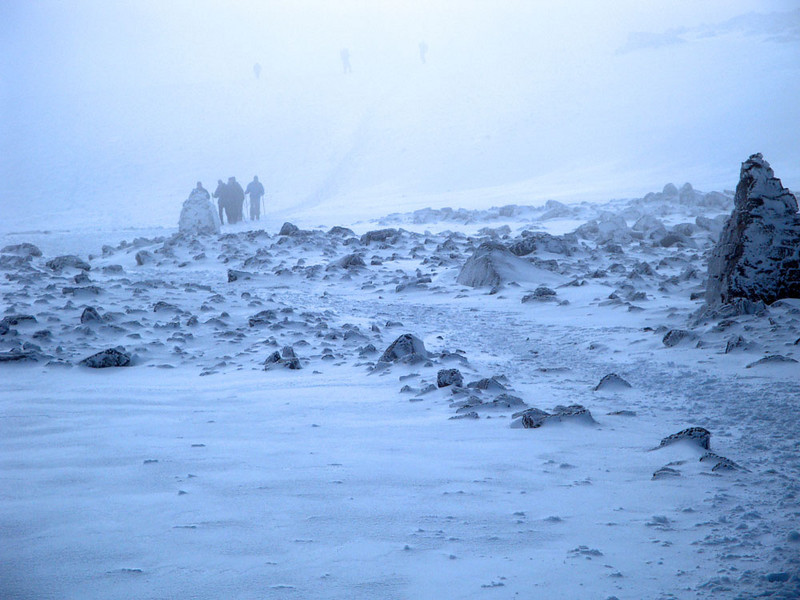 The snow became a minor blizzard. We could only see from one rock cairn to the next - about 30 feet (the white haze has been photoshopped away). The path consisted of footprints in snow that were rapidly being buried. This fully roped party descended past us dripping with sleet and snow. Not good...