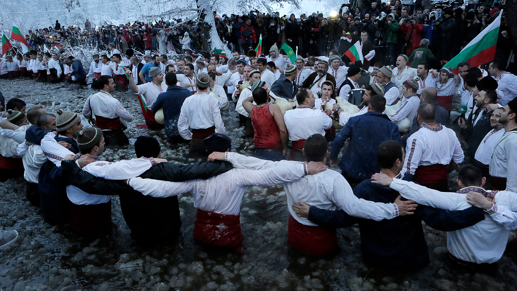 . Believers dance in the icy water of the river Tundzha as they celebrate Epiphany day, a Christian festival, in the town of Kalofer, Bulgaria, Friday, Jan. 6, 2017. Traditionally, an Eastern Orthodox priest throws a cross in the river and it is believed that the one who retrieves it will be healthy through the year. In the central Bulgarian town of Kalofer, hundreds of Christians marked Epiphany by donning national costumes and wading into the frigid waters of the Tundzha river. (AP Photo/Valentina Petrova)