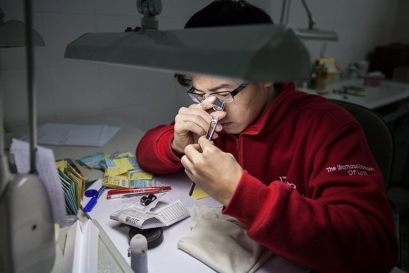 Simon Liu, team leader of diamond finishing checking in the quality control department of Guangzhou Mickey Weinstock & Co Diamonds Manufacturing Limited, inspects a diamond at the company's diamond polishing factory in Shawan, Panyu District, Guangzhou, Guangdong Province, China on Monday, Jan. 24, 2011. Photographer: Forbes Conrad/Bloomberg News