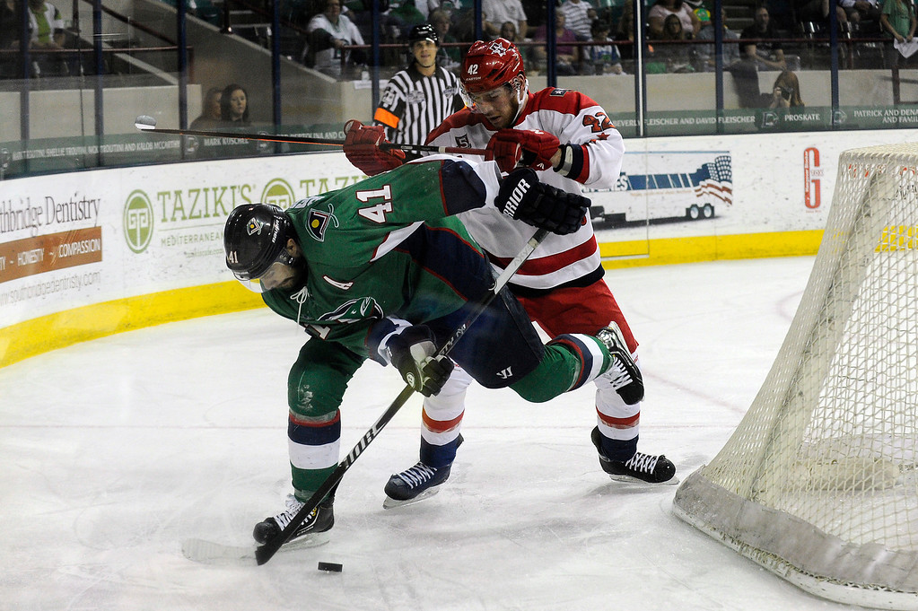 . DENVER, CO - MAY 2: Garett Bembridge (41) of the Denver Cutthroats is hit from behind by Ross Rouleau (42) of the Allen Americans as they battle for a loose puck behind the net during the first period of game 1 of the Ray Miron Presidents Cup Finals at the Denver Coliseum in Denver, Colorado on May 2, 2014. (Photo by Seth McConnell/The Denver Post)
