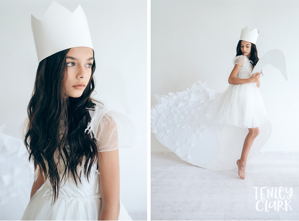 Girl with paper crown and giant paper swan.Whimsical kid's fashion editorial with giant white paper origami props. Photography by Tenley Clark.