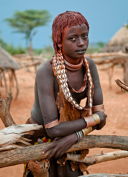 Hamar woman in her village. The double necklaces worn symbolises her status as a third wife. Her hair has been reddened with a mixture of red ochre (clay) and animal fat.