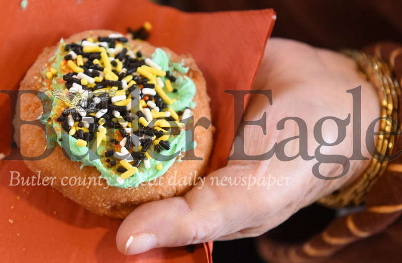 Harold Aughton/Butler Eagle: Pearl Kocher, 84, of Butler decorates a donut as part of the senior fall festival at Camp Kon-o-Kwee, Wed., Oct. 30.