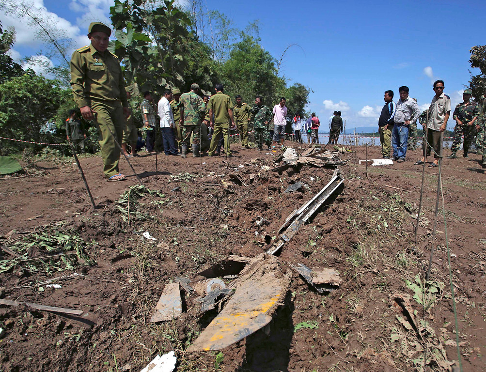 . A soldier looks at a metal object which is believed to be part of a Laos Airlines plane that crashed in Pakse, Laos Thursday, Oct. 17, 2013.  (AP Photo/Sakchai Lalit)