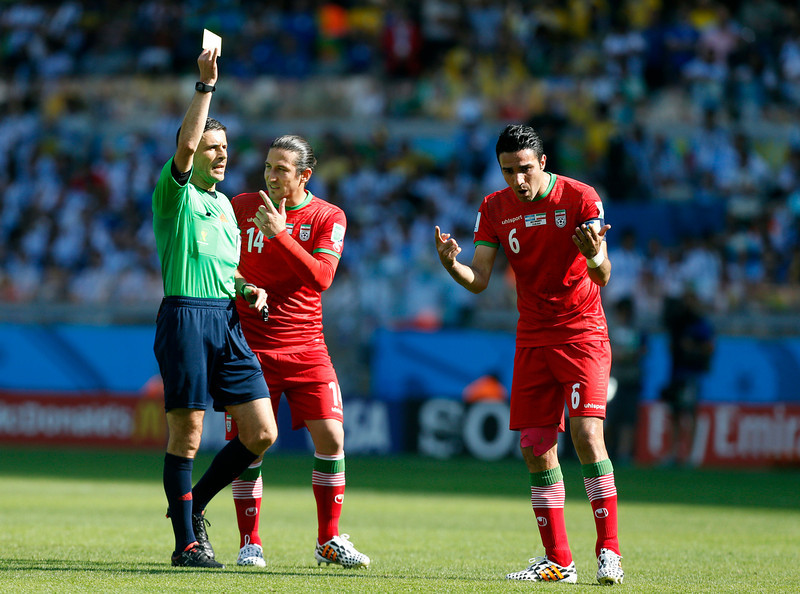 . Referee Milorad Mazic from Serbia shows a yellow card to Iran\'s Javad Nekounam, right, during the group F World Cup soccer match between Argentina and Iran at the Mineirao Stadium in Belo Horizonte, Brazil, Saturday, June 21, 2014. (AP Photo/Jon Super)
