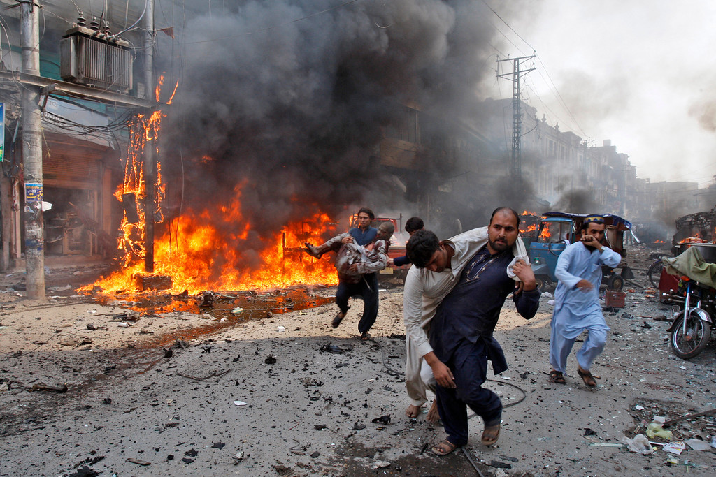 . Injured Pakistani men are carried away from the site of a blast shortly after a car explosion in Peshawar, Pakistan, Sunday, Sept. 29, 2013. A car bomb exploded on a crowded street in northwestern Pakistan Sunday, killing scores of people in the third blast to hit the troubled city of Peshawar in a week, officials said. (AP Photo/Mohammad Sajjad)