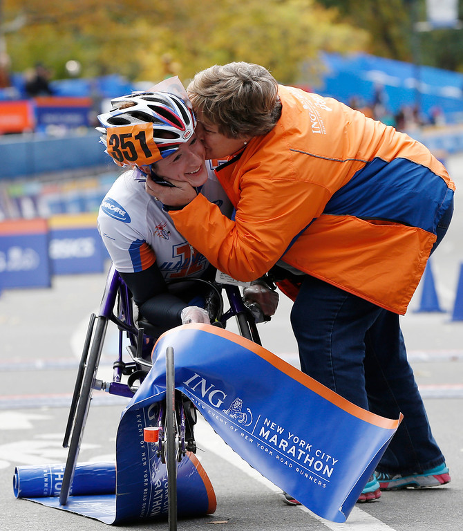 . Women\'s wheelchair winner Tatyana McFadden, left, gets a kiss from a family member after coming in first in the women\'s wheelchair division of the New York City Marathon, Sunday, Nov. 3, 2013, in New York. (AP Photo/Kathy Willens)