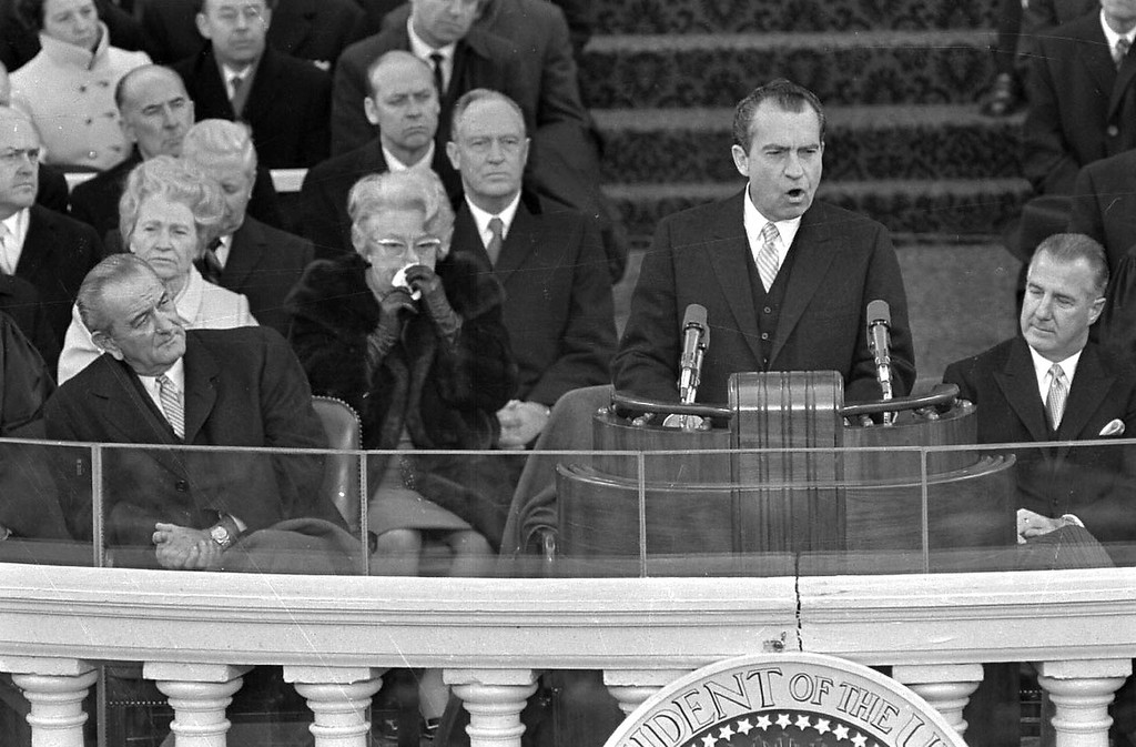 ". President Richard M. Nixon dedicates his new administration to the cause of ""peace among nations\"" as former President Lyndon Johnson, right, listens to the inaugural speech Jan. 20, 1969 in Washington.  Seated at right is Vice President Spiro Agnew and former Vice President Hubert Humphrey. (AP Photo)"