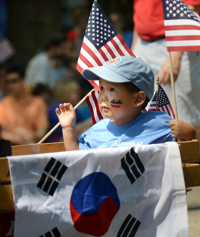 . Korean-born Andrew Tae Kyung Conrad, 3, waves to folks along the parade route as he is pulled in a wagon by his father, Mike Conrad.  (Pioneer Press: Chris Polydoroff)