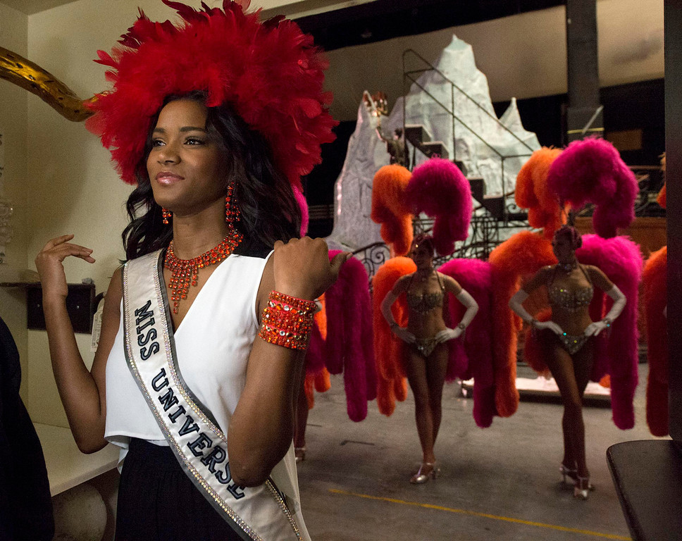 . Miss Universe 2011 Leila Lopes of Angola tries on a Jubilee head piece as the Jubilee Show dancers wait for her during a tour at Bally\'s in Las Vegas, Nevada December 6, 2012. The Miss Universe 2012 competition will be held on December 19. REUTERS/Matt Brown/Miss Universe Organization L.P/Handout