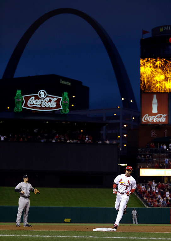 . St. Louis Cardinals\' Carlos Beltran, right, rounds the bases after hitting a solo home run as Colorado Rockies third baseman Nolan Arenado, left, watches during the third inning of a baseball game on Friday, May 10, 2013, in St. Louis. (AP Photo/Jeff Roberson)