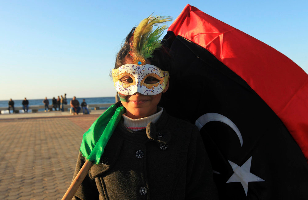 . A girl smiles as she marks the second anniversary of the country\'s revolution in Benghazi February 16, 2013. The actual second anniversary of the start of the anti-Gaddafi revolt is not until Sunday, but celebrations began on Friday in remembrance of the arrest of a human rights lawyer in Benghazi that kindled the unrest.   REUTERS/Esam Al-Fetori
