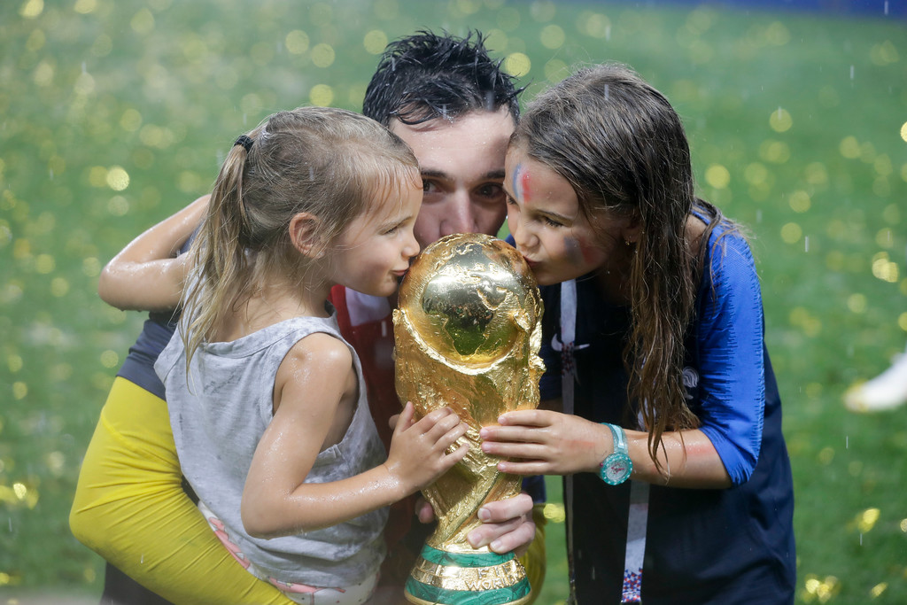 . France goalkeeper Hugo Lloris, center, and children kiss the trophy at the end of the final match between France and Croatia at the 2018 soccer World Cup in the Luzhniki Stadium in Moscow, Russia, Sunday, July 15, 2018. (AP Photo/Matthias Schrader)