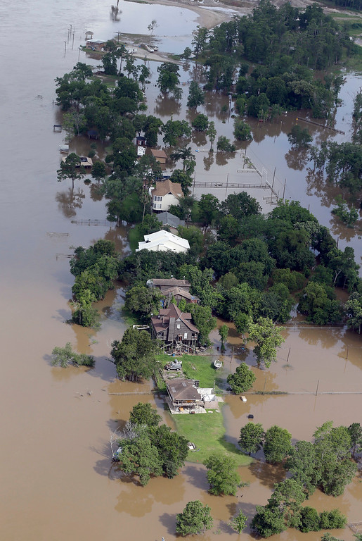. In this aerial photo, homes are surrounded by floodwaters near the San Jacinto River Saturday, May 30, 2015, in Channelview, Texas. The Colorado River in Wharton and the Brazos and San Jacinto rivers near Houston are the main focus of concern as floodwaters moved from North and Central Texas downstream toward the Gulf of Mexico. (AP Photo/David J. Phillip)