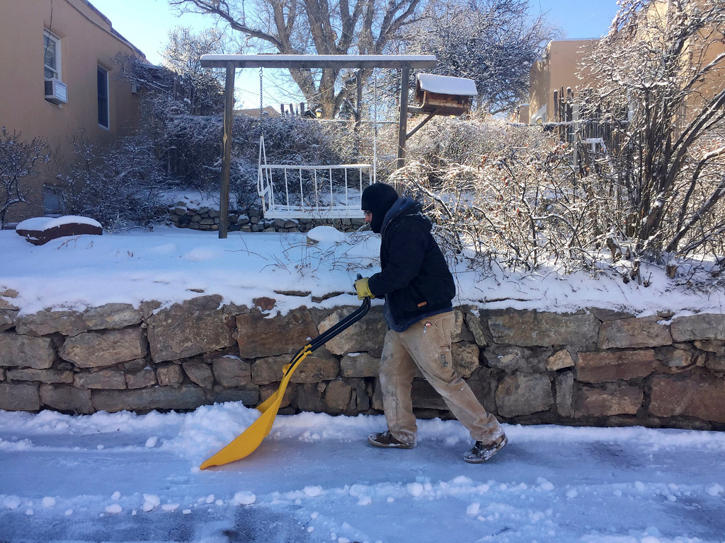. Laborer Guillermo Perez, of Santa Fe, N.M, clears sidewalks and driveways as residents dig out from a winter storm that closed schools and blanketed nearby ski resorts with snow on Friday, Jan. 6, 2017. Authorities reported difficult driving conditions on the state\'s two main interstate highways. (AP Photo/Morgan Lee)