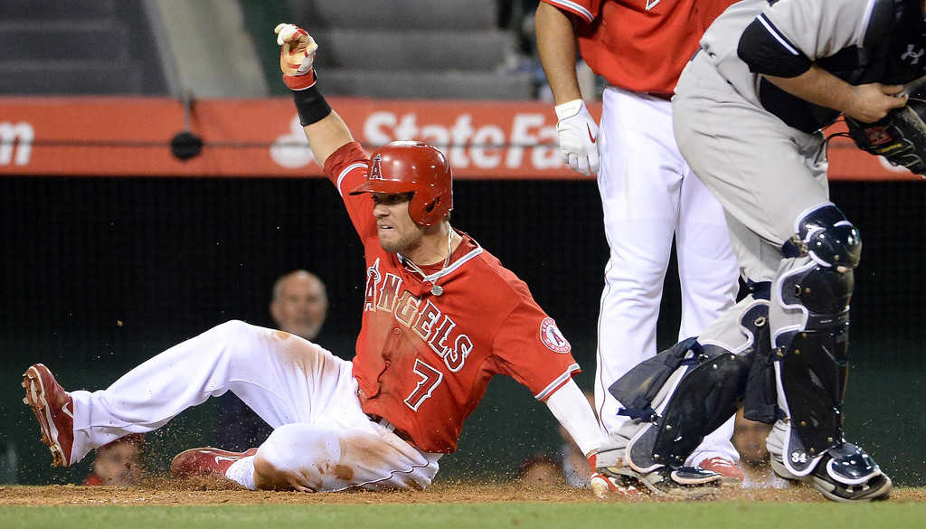 . Los Angeles Angels\' Collin Cowgill (7) scores on a sac fly ball by Mike Trout (not pictured) in the third inning of a baseball game against the New York Yankees at Anaheim Stadium in Anaheim, Calif., on Tuesday, May 6, 2014.  (Keith Birmingham Pasadena Star-News)