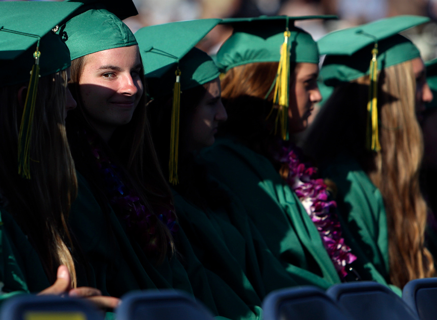 . A shadow lays across the face of a Harbor High graduate as she jokes with her friends during the 2013 graduation ceremony at Cabrillo College in Aptos on Friday. (Kevin Johnson/Sentinel)