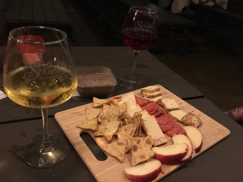 two glasses of wine with cheese plate